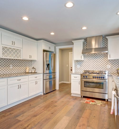 Gorgeous white kitchen room with Moroccan Tiles Backsplash and modern stainless steel appliances.