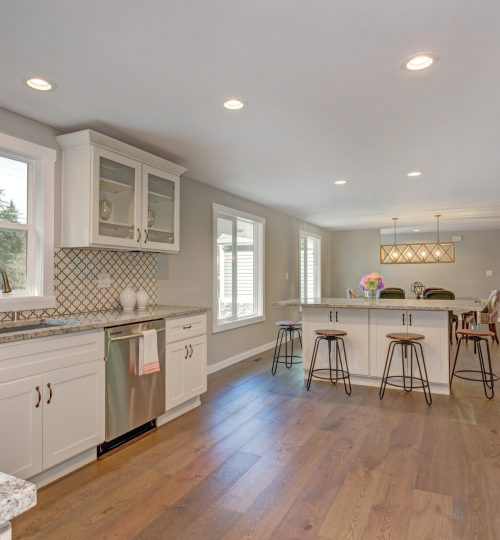 Gorgeous large kitchen with island, bar stools, granite counters and new appliances over hardwood floor.